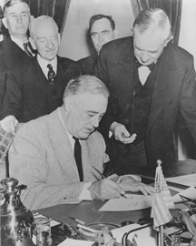 President Roosevelt signs Declaration of War while surrounded by four congressmen.