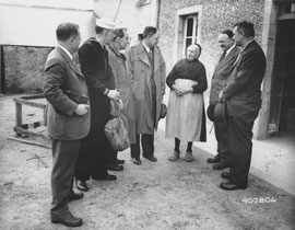 Photo of senators talking to old woman outside her house.