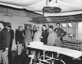 Photo of a group of senators and military men inspect hospital operating room.