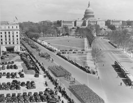 Photo of a military parade on a street next to the Capitol Building.