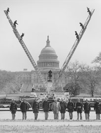 Photo of firetrucks forming a 'V' with their ladders in front of the Capitol Building.