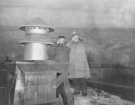 Photo of two men standing next to an air raid siren with hands over their ears.