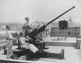 Photo of three soldiers manning an anti-aircraft gun on the top of a DC building, with the Capitol Building in the background.