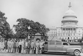 Photo of workers lined up in front of Capitol waiting for a ride in an extended length car.