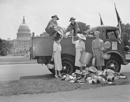 Photo of several three women and two boys loading tin-ware into a truck in front of the Capitol Building.