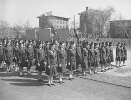 Photo of school kids in military uniforms in formation, prepared to perform military drills.