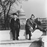 Photo of two servicemen resting in front of the U.S. Capitol Building