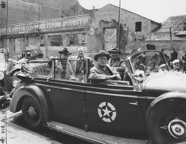 Photo of four senators riding in open-topped car.