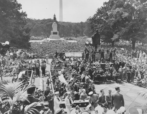 Photo of a large crowd of people gathered with Washington Memorial in background.