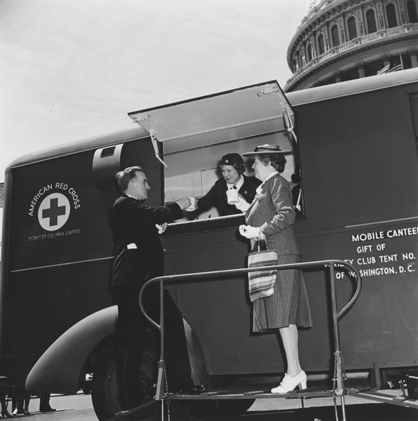 Photo of a Red Cross worker serving coffee to a man and woman from a truck in front of the Capitol Building.